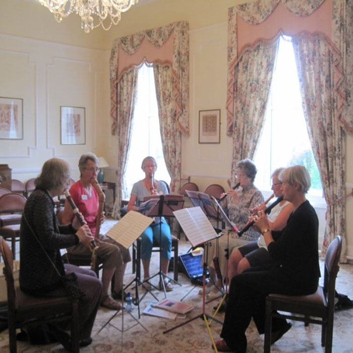Image of a group rehearsing in a elegant room